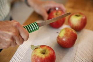 Eine Hand mit Messer und Äpfel auf einem Brett