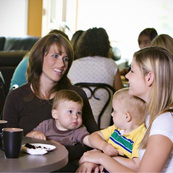 Mütter mit Ihren Kindern sitzem im Café und unterhalten sich