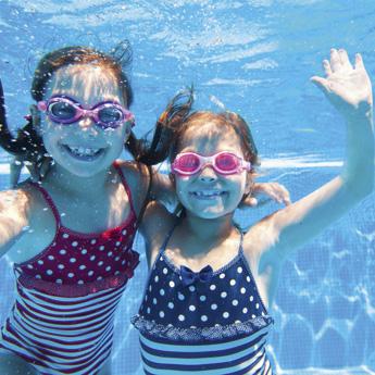 2 Mädchen im Schwimmbecken unter Wasser mit Taucherbrille