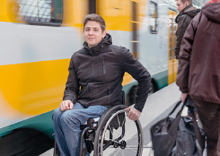 Junger Mann im Rollstuhl auf dem Bahnsteig